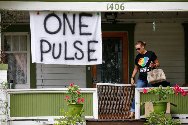 "A woman walks out of a small home with a ""One Pulse"" banner hung from the porch in Orlando, Florida, June 17, 2016. (Photo by Carlo Allegri/Reuters)"