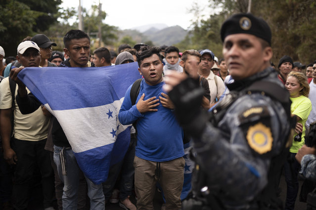 """Honduran migrants walking in a group stop before Guatemalan police near Agua Caliente, Guatemala, Thursday, January 16, 2020, on the border with Honduras. Less-organized migrants, tighter immigration control by Guatemalan authorities and the presence of U.S. advisers have reduced the likelihood that the hundreds of migrants who departed Honduras will form anything like the cohesive procession the term """"caravan"""" now conjures. (Photo by Santiago Billy/AP Photo)"""