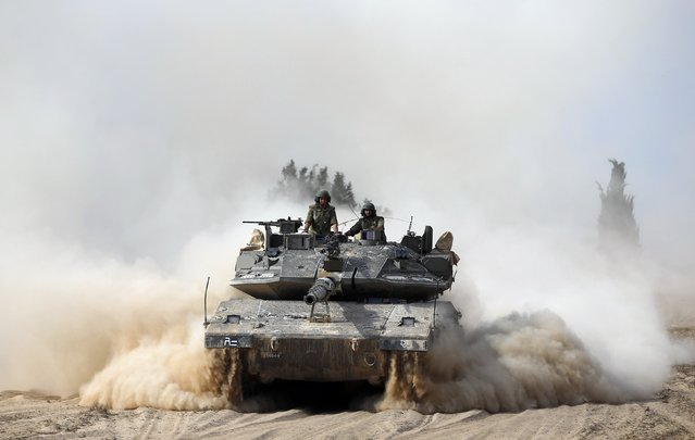 Israeli soldiers ride atop a tank outside the southern Gaza Strip July 7, 2014. Israel launched a series of air strikes on Gaza early on Monday to quell Hamas rocket fire, and the Islamist group's armed wing said seven of its gunmen were killed, making it the deadliest day for Hamas since a 2012 cross-border war with the Jewish state. (Photo by Baz Ratner/Reuters)