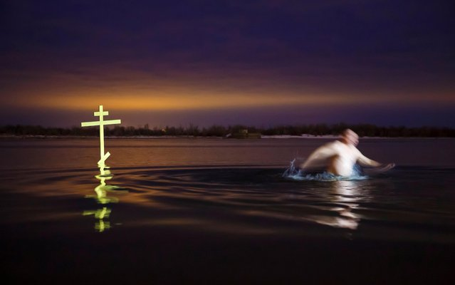 A man walks next to a cross after taking a dip in the shallow water of the Volga river during celebrations of the Orthodox Christian feast of Epiphany in Volgograd, Russia on January 19, 2020. (Photo by Kirill Braga/Reuters)