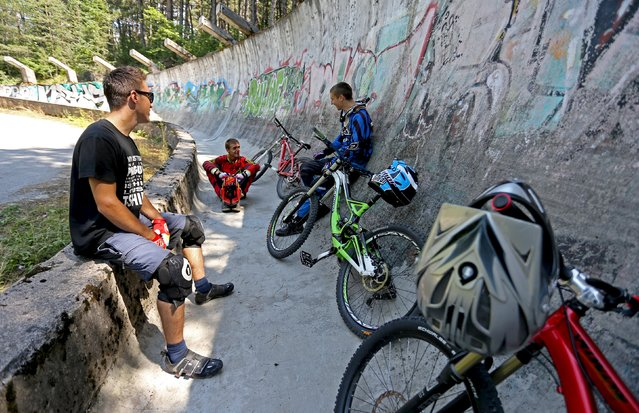 Downhill bikers Kemal Mulic (C), Kamer Kolar (R) and Tarik Hadzic rest during training on the disused bobsled track from the 1984 Sarajevo Winter Olympics on Trebevic mountain near Sarajevo, Bosnia and Herzegovina, August 8, 2015. (Photo by Dado Ruvic/Reuters)