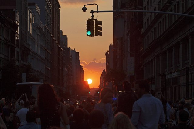 """People take pictures at sunset during the bi-annual occurrence """"Manhattanhenge"""" in New York July 11, 2014. Manhattanhenge, coined by astrophysicist Neil deGrasse Tyson, occurs when the setting sun aligns itself with the east-west grid of streets in Manhattan, allowing the sun to shine down all streets at the same time. (Photo by Eduardo Munoz/Reuters)"""