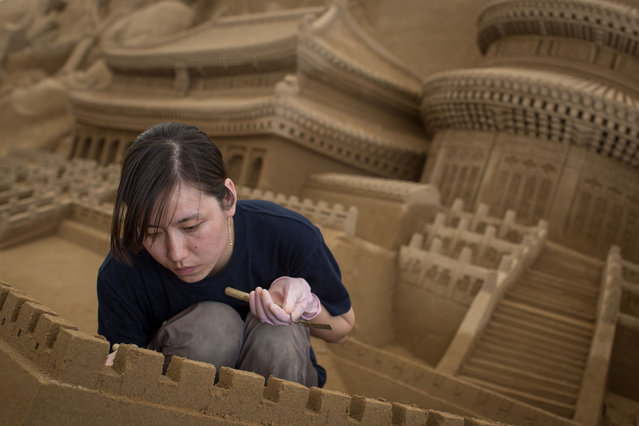 Sand sculptor Zhang Yan of China works on the Chinese section of a large sand sculpture at the site of Yokohama Sand Art Exhibition – Culture City of East Asia 2014 on July 16, 2014 in Yokohama, Japan. Producer and sand sculptor Katsuhiko Chaen invited artists from around the world including South Korea and China, to recreate the World Heritage and historical buildings in China, Japan and South Korea. The exhibition will be open from July 19 to November 3, 2014. (Photo by Chris McGrath/Getty Images)