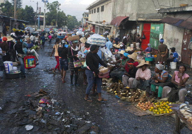 In this December 4, 2019 photo, street vendors sell their produce in Petion-Ville, Haiti. A growing number of families across Haiti can't afford to buy food since protests began in Sept., with barricades preventing the flow of goods between the capital and the rest of the country. (Photo by Dieu Nalio Chery/AP Photo)