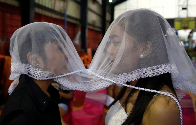 A couple wear a veil during a same s*x wedding ceremony officiated by Reverend CJ Agbayani (not pictured) of the Christian Church Inc in Quezon city, Metro Manila, Philippines June 26, 2016. (Photo by Erik De Castro/Reuters)