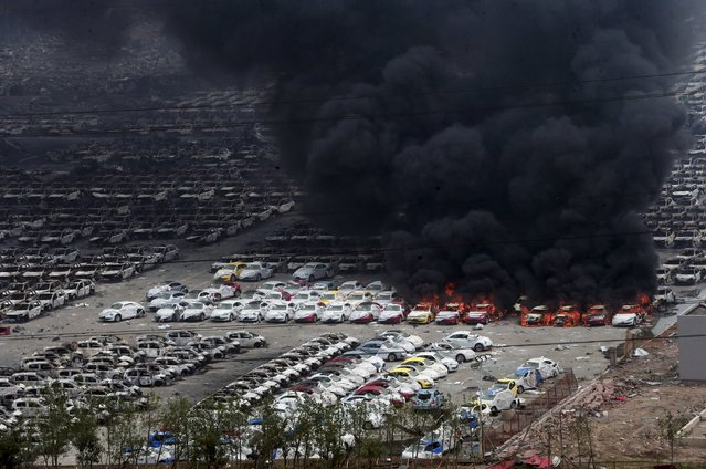 Smoke rises as damaged vehicles are seen burning near the site of Wednesday night's explosions, at Binhai new district in Tianjin, China, August 15, 2015. (Photo by Reuters/Stringer)