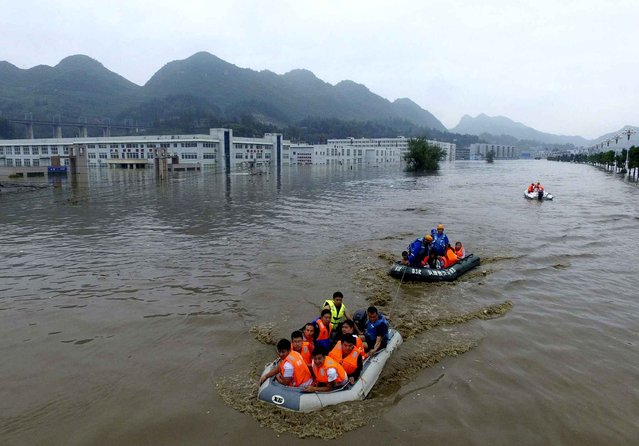 In this photo taken Tuesday June 28, 2016, rescuers evacuate residents trapped by flood waters in Zhijin county, southwest China's Guizhou province. Chinese state media reported Tuesday that heavy rain continue to wreak havoc in southern China forcing thousands of residents to be evacuated. (Photo by Chinatopix via AP Photo)