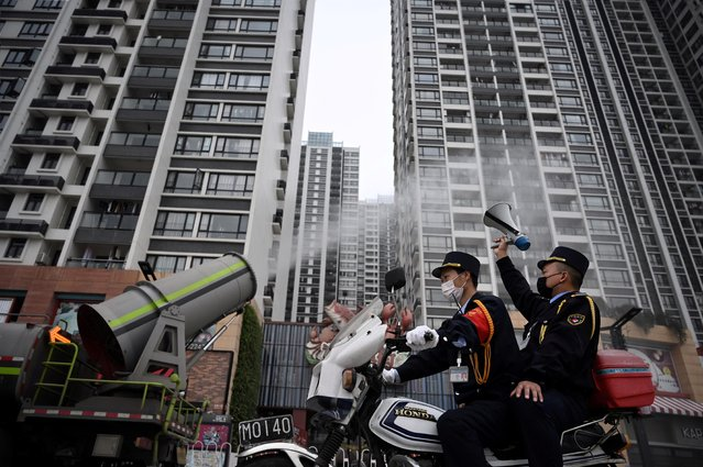 A man holding a loudspeaker sits on a motorcycle as it travels past a sanitizing vehicle disinfecting the area near residential buildings, in Panyu district of Guangzhou, Guangdong province, February 11, 2020. (Photo by Reuters/China Daily)