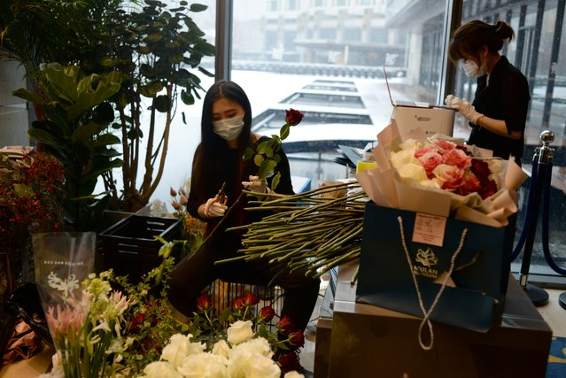Florist Zhen Zhen (L) and shop owner Jiankun Song prepare flower bouquets to deliver on Valentine's Day, at the Mulan Blossom flower shop in Beijing, February 14, 2020. (Photo by Tingshu Wang/Reuters)