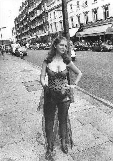 1975: Jane Keiren, a Public Relations executive from London auction house Christie's of Kensington, wearing a dress worn by Marilyn Monroe in the film, 'Bus Stop' whilst standing by a Bus Stop on Brompton Road, London