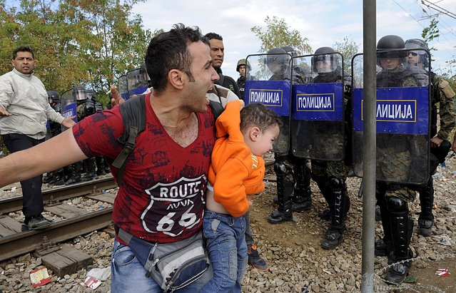 A migrant reacts as he carries a child during clashes with Macedonian police at the Greek-Macedonian border, August 21, 2015. (Photo by Alexandros Avramidis/Reuters)