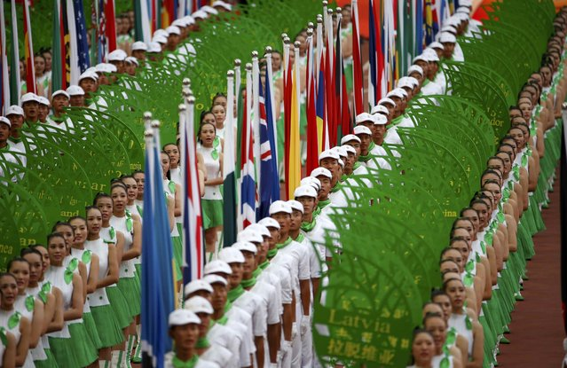 Flags of participating nations are held up during the opening ceremony of the 15th IAAF World Championships at the National Stadium in Beijing, China August 22, 2015. (Photo by David Gray/Reuters)