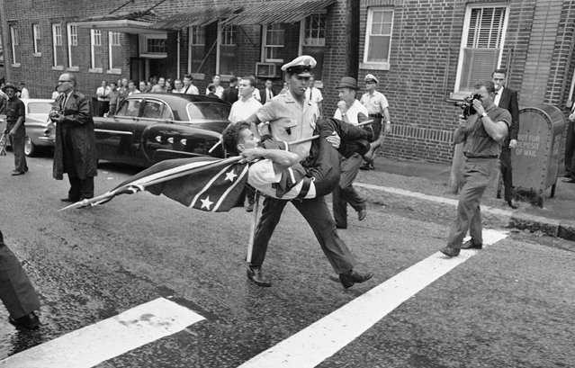 In this September 4, 1963, file photo, a police officer carries off a demonstrator holding a Confederate flag after a group of demonstrators protested enrollment of two African-Americans at Ramsay High School in Birmingham, Ala. The Confederate battle flag has been removed from South Carolina's Statehouse grounds, in the wake of the massacre of nine African-Americans, including a state senator, at an historic black church in Charleston in June 2015. (Photo by AP Photo)