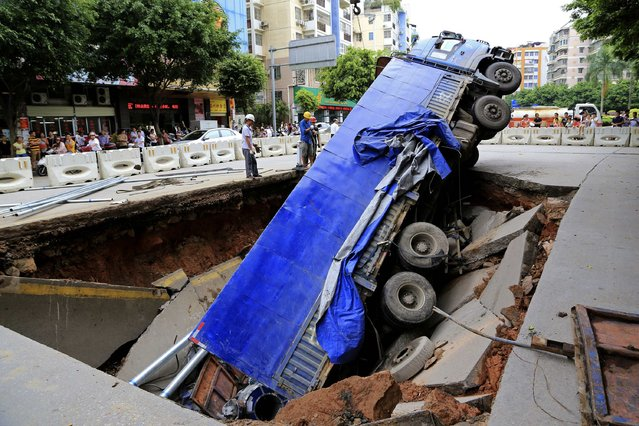 Workers stand next to a truck which is stuck in a large pit caused by a cave-in on a street in Wuzhou, Guangxi Zhuang Autonomous Region, August 14, 2014. According to Xinhua News Agency, the pit is about 40-square-metres wide and no casualty has been reported. (Photo by Reuters/Stringer)