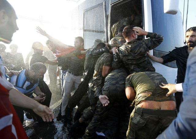 Soldiers push each other to board a bus to escape the mob after troops involved in the coup surrendered on the Bosphorus Bridge in Istanbul, Turkey July 16, 2016. (Photo by Murad Sezer/Reuters)