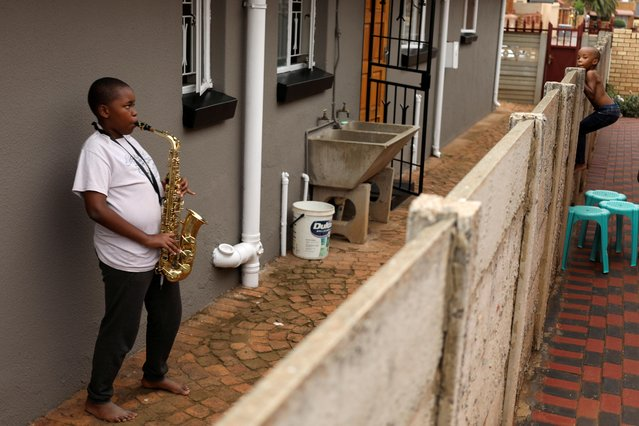 Ntsika Ntsele, 13, plays an alto saxophone while his neighbor looks on over a fence, during a nationwide lockdown for 21 days to try to contain the coronavirus disease (COVID-19) outbreak, in Soweto, South Africa, March 29, 2020. (Photo by Siphiwe Sibeko/Reuters)