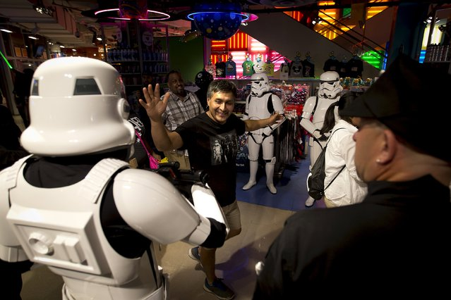 """A man high fives a character from """"Star Wars"""" as he arrives to purchase toys that went on sale at midnight in advance of the film """"Star Wars: The Force Awakens"""" in Times Square in the Manhattan borough of New York, September 4, 2015. (Photo by Carlo Allegri/Reuters)"""