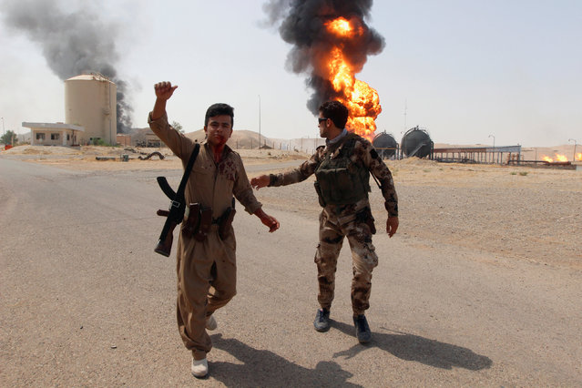 An injured member of Kurdish Peshmerga forces reacts as smoke rises after an attack at Bai Hassan oil station, northwest of Kirkuk, Iraq, July 31, 2016. Militants have attacked a gas facility and an oilfield in northern Iraq, killing five people. Gunmen on motorbikes opened fire on the facility's guards, then killed four of its employees and planted bombs before escaping. Militants also attacked the nearby Bai Hassan oilfield, the largest in oil-rich Kirkuk province, killing an engineer and causing a major fire. (Photo by Ako Rasheed/Reuters)