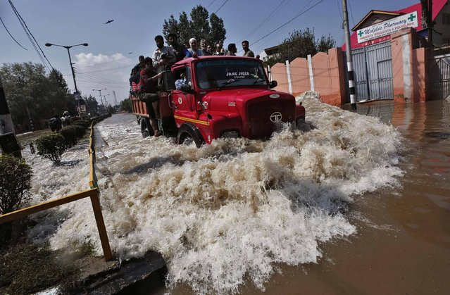 A truck evacuating Kashmiri flood victims to higher ground travels through a flooded street in Srinagar September 10, 2014. Flood waters started receding in Indian Kashmir on Wednesday, giving rescue teams a chance to reach tens of thousands of villagers stranded by the heaviest rainfall in half a century. Floods and landslides triggered by days of rain in the disputed Himalayan region have killed at least 450 people in India and Pakistan and cut off more than one million people from basic services. (Photo by Adnan Abidi/Reuters)