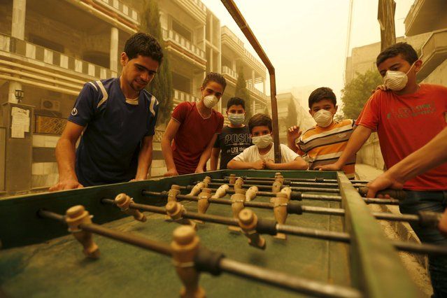 Children wearing face masks play table football during a sandstorm in Homs, Syria September 7, 2015. (Photo by Omar Sanadiki/Reuters)