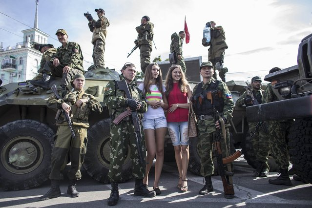 Women pose for a picture with pro-Russian rebels during a parade in Luhanks, eastern Ukraine, September 14, 2014. (Photo by Marko Djurica/Reuters)