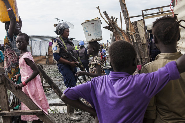 A member of the United Nations Police, UNPOL, stands guard during a routine search of contraband of the Protection of Civilians (POC) site at the United Nations Mission in South Sudan (UNMISS) compound in Malakal, South Sudan on Friday, July 15, 2016. (Photo by Jane Hahn/The Washington Post)