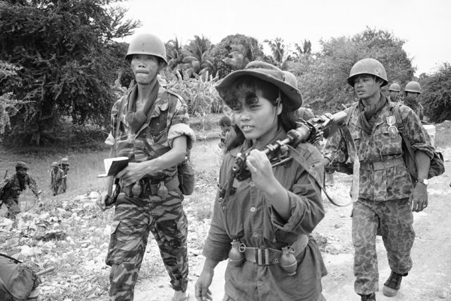 A female Cambodian soldier totes a machine gun into combat during an operation across the Mekong River from Phnom Penh in the Prek Tamak area of Cambodia on August 26, 1970. This region was the scene of heavy fighting between Cambodian troops and Viet Cong. The young woman is one of many who served as regular soldiers and medics in the rapidly expanded army. (Photo by Ghislain Bellorget/AP Photo)