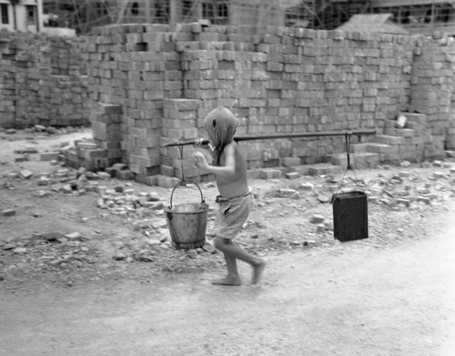 Age is no bar to employment in China, here youngsters are put to work carrying water to the stone breakers on June 1, 1949. Their ages are about 7 years and their wages almost nothing per day, they are in the employ of Chinese-get rich quick real estate operators from Shanghai. (Photo by AP Photo)