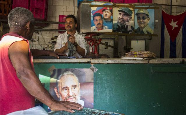 Posters with the portrait of Cuban Revolution leader Fidel Castro, Cuban President Raul Castro, Venezuelan President Nicolas Maduro and late Venezuelan President Hugo Chavez hang in a butcher shop in Havana, Cuba, Saturday, August 13, 2016. (Photo by Desmond Boylan/AP Photo)