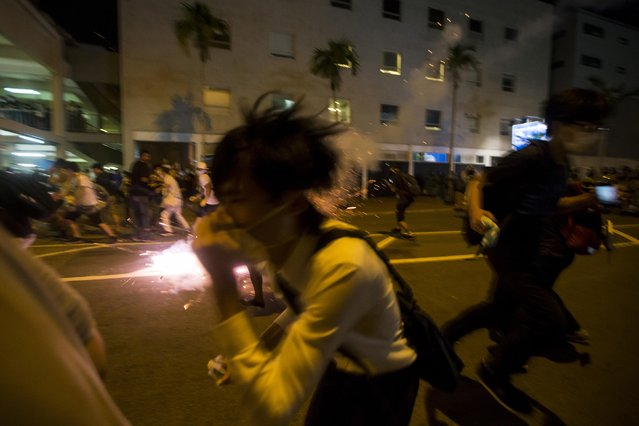 Protesters run for cover as riot police fire teargas after thousands of protesters blocked the main street to the financial Central in Hong Kong September 29, 2014. Some Hong Kong financial firms advised staff to work from home on Monday or go to secondary offices after thousands of pro-democracy demonstrators blocked parts of the city and clashed with police. (Photo by Tyrone Siu/Reuters)