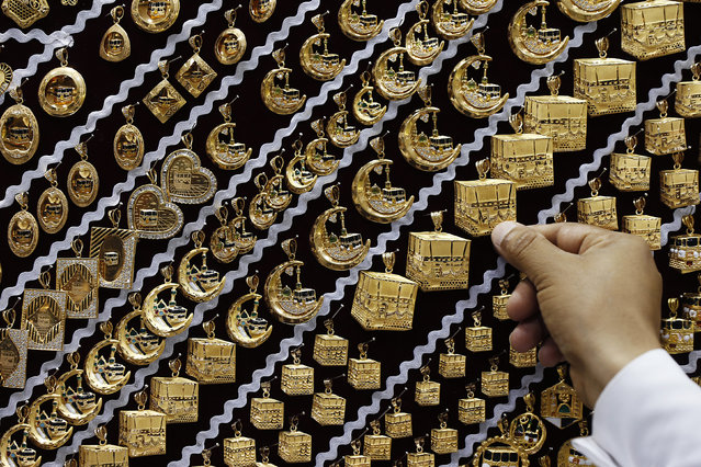 A dealer displays gold pendants at a jewellery shop near the Grand Mosque during the annual Hajj pilgrimage in Mecca September 27, 2014. (Photo by Muhammad Hamed/Reuters)