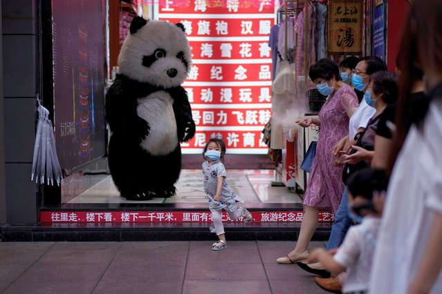 A little girl wearing a face mask dances in front of a toy panda at a shopping area in Shanghai, following the coronavirus disease (COVID-19) outbreak, China on June 16, 2020. (Photo by Aly Song/Reuters)
