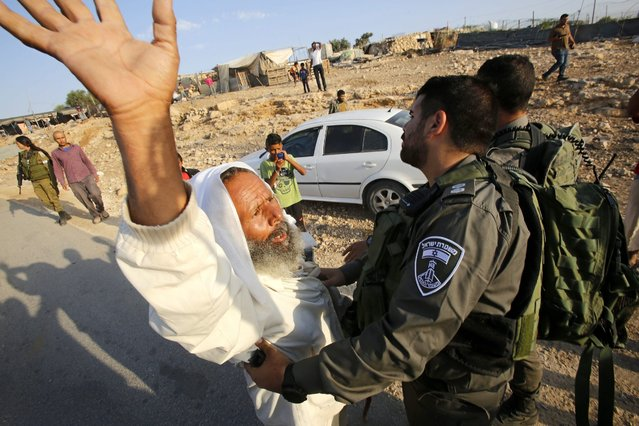 Palestinian shed owner Sulaiman Hathaleen (L) scuffles with Israeli border police after Israeli troops demolished his shed in the West Bank village of Um Alkhair, south of Hebron, 24 August 2016. The Israeli army claims that the Palestinians did not have the needed Israeli permits to build in this area of the West Bank. (Photo by Abed Al Hashlamoun/EPA)
