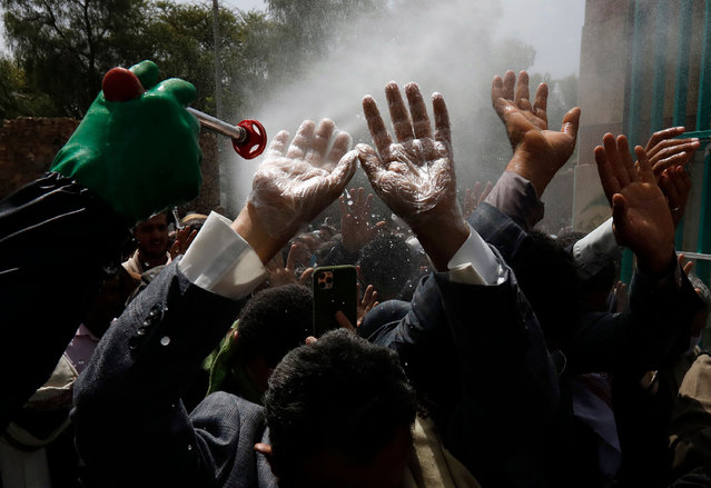 A Yemeni worker wearing a protective suit sprays disinfectant on the hands of people before they enter a cemetery during a funeral procession, amid the ongoing coronavirus COVID-19 pandemic in Sanaa, Yemen, 10 June 2020. War-torn Yemen has not enforced curfews or lockdown measures to curb the widespread of the SARS-CoV-2 coronavirus which causes the COVID-19 disease, despite raised fears the pandemic is rapidly spreading undetected throughout Yemen. (Photo by Yahya Arhab/EPA/EFE/Rex Features/Shutterstock)