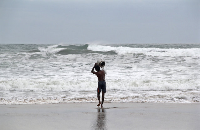 A man pours sea water on himself as he performs a ritual for safety ahead of cyclone Hudhud, by the shore at Visakhapatnam district in Andhra Pradesh October 11, 2014. (Photo by R. Narendra/Reuters)