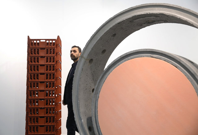 """A visitor passes artworks """"Stack VII"""" by Michael Landy (L) and """"Public Sculpture"""" by Alexandre de Cunha at the Frieze Art Fair in London, October 14, 2014. (Photo by Luke MacGregor/Reuters)"""