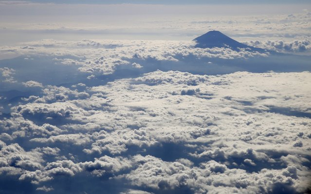 Japan's Mount Fuji, surrounded by clouds, is seen from an airplane October 6, 2015. Mount Fuji, at 3,776 metres (12,388 ft) is Japan's highest mountain. (Photo by Toru Hanai/Reuters)