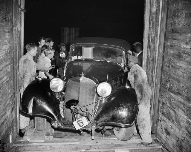 The 10,000-pound, 19-foot-long Mercedes-Benz automobile of Adolf Hitler gives workmen some trouble as they unload it from a freight car in Rosslyn, Va., October 19, 1945. W.H. Griffith, far left, a civilian automotive inspector at nearby Ft. Myer, gives the heave-ho signal. Hitler's car, along with Hermann Goering's, was brought over for the forthcoming Victory Loan Drive and will be driven through the country. (Photo by Harvey Georges/AP Photo)