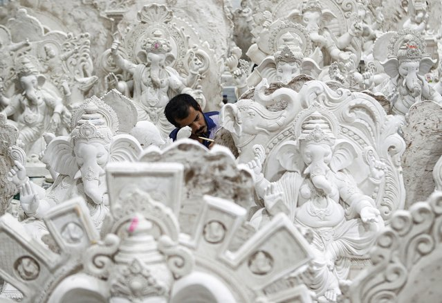 A man works on an idol of Hindu god Ganesh, the diety of prosperity, before the Ganesh Chaturthi festival in Mumbai, India, July 19, 2020. (Photo by Francis Mascarenhas/Reuters)