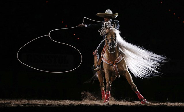 A rodeo performer does rope tricks at the end of the 10th go-round of the National Finals Rodeo in Las Vegas, December 15, 2012. (Photo by Julie Jacobson/Associated Press)
