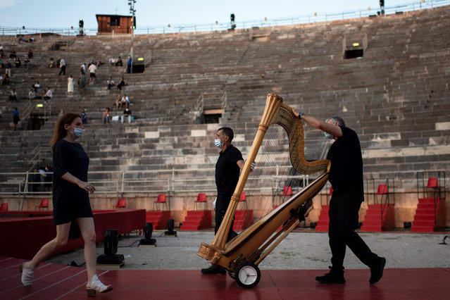 Workers transport a harp on stage during a rehearsal before a concert at the Arena in Verona, northern Italy, on July 25, 2020. This is the first show with new dispositions against the spread of the novel coronavirus (Covid-19) during this season. (Photo by Marco Bertorello/AFP Photo)