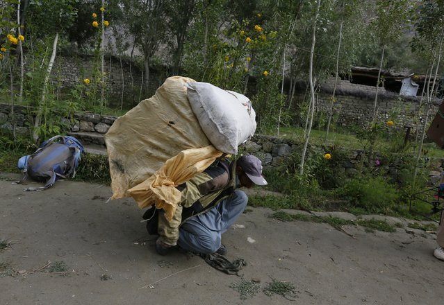 Porter Hassan Trampa, 35, lifts his load in the village of Askole in the Karakoram mountain range in Pakistan August 28, 2014. (Photo by Wolfgang Rattay/Reuters)