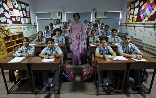 Teacher Archana Shori poses for a picture with 7th-grade level students inside their classroom at Rukmini Devi Public school in New Delhi, India, September 7, 2015. Nearly three years after Taliban gunmen shot Pakistani schoolgirl Malala Yousafzai, the teenage activist last week urged world leaders gathered in New York to help millions more children go to school.  (Photo by Adnan Abidi/Reuters)