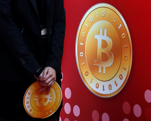 An attendant holds a bitcoin sign during the opening of Hong Kong's first bitcoin retail store February 28, 2014. (Photo by Bobby Yip/Reuters)