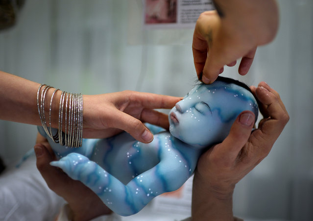 """Babyclon owner Cristina Iglesias adjusts an Avatar baby at the Bilbao Reborn Doll Show, a trade fair featuring hyperrealist silicone and vinyl babies, known as """"Reborns"""", in Bilbao, northern Spain June 11, 2017. (Photo by Vincent West/Reuters)"""