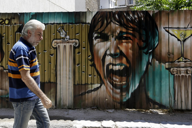 A man passes graffiti in Athens, Tuesday, July 21, 2015. (Photo by Thanassis Stavrakis/AP Photo)