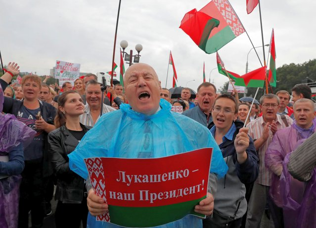 """People attend a rally in support of Belarusian President Alexander Lukashenko in Minsk, Belarus on August 19, 2020. The placard reads: """"Lukashenko is our president!"""". (Photo by Vasily Fedosenko/Reuters)"""