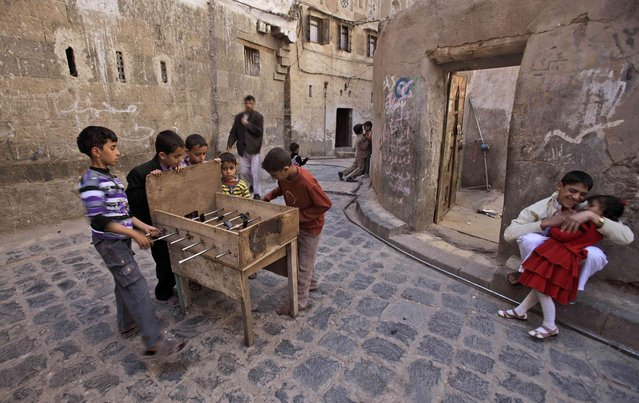 Yemeni children, center, play table football on a table they created, in an alley of the old city of Sanaa, Yemen, on Friday, November 26, 2010. (Photo by Muhammed Muheisen/AP Photo)