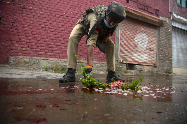 An Indian policeman cleans blood splattered on a street with a tree twig after suspected rebels attack on policemen on the outskirts of Srinagar, Indian controlled Kashmir, Friday, August 14, 2020. Anti-India rebels in Indian-controlled Kashmir Friday attacked a police party in the disputed region's main city, killing two police officials and injuring another, police said. (Photo by Mukhtar Khan/AP Photo)