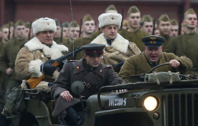 Men, dressed in historical uniforms, drive a vehicle during a military parade in Red Square in Moscow, November 7, 2014. (Photo by Maxim Shemetov/Reuters)